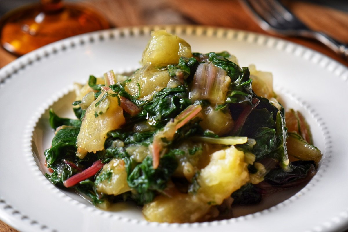 Swiss chard and potatoes in a white bowl.
