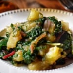 Swiss chard and potatoes in a white dish.