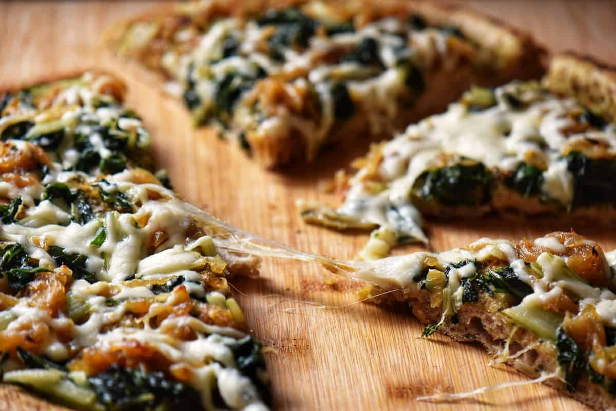 A slice of cheesy homemade healthy pizza on a wooden board.