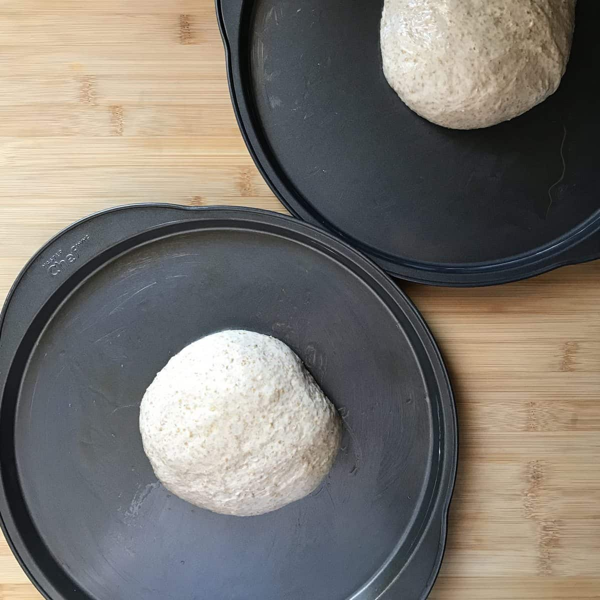 Two balls on dough on pizza pans.
