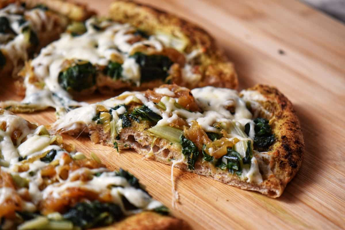 A slice of healthy homemade pizza on a wooden cutting board.