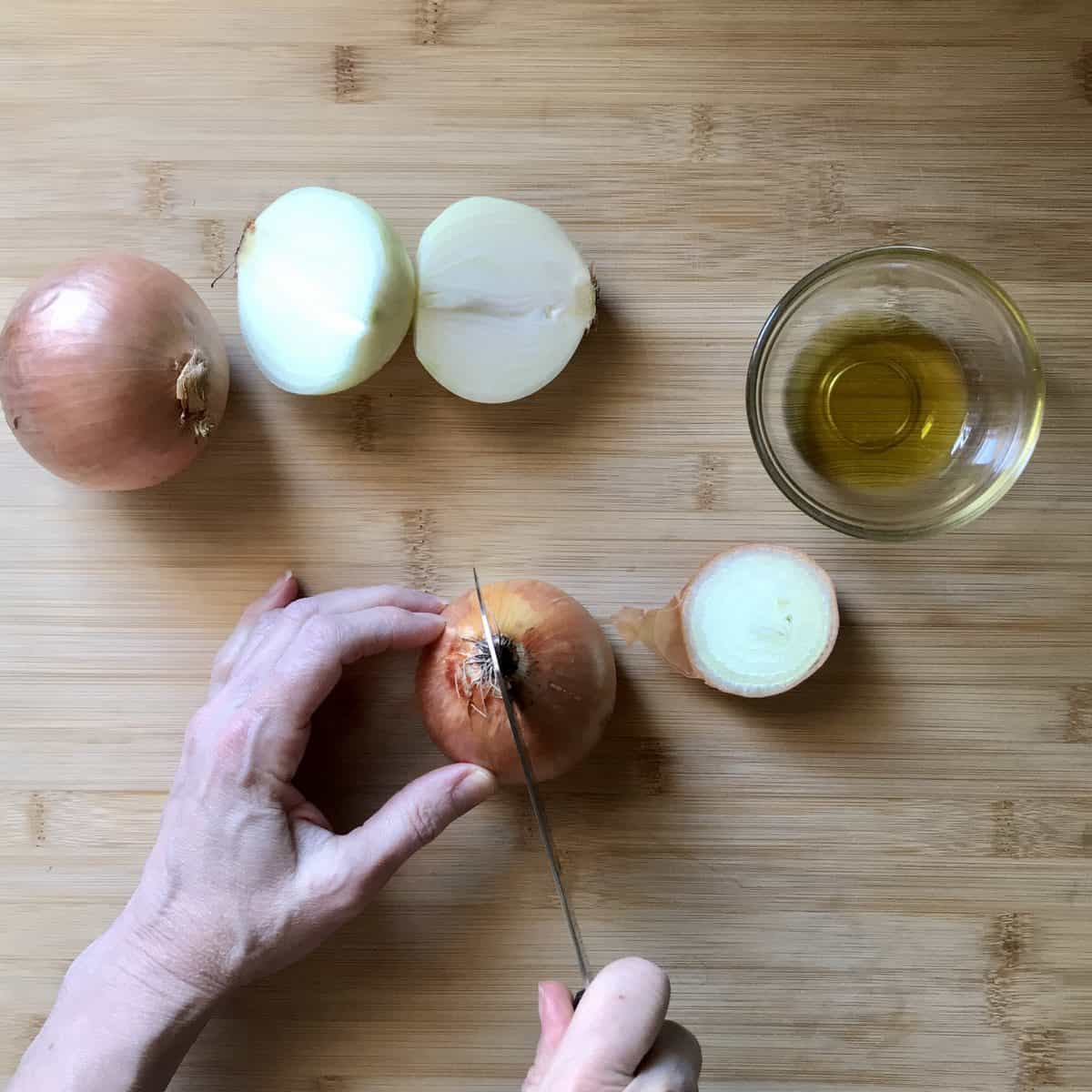 An onion being sliced through the root.