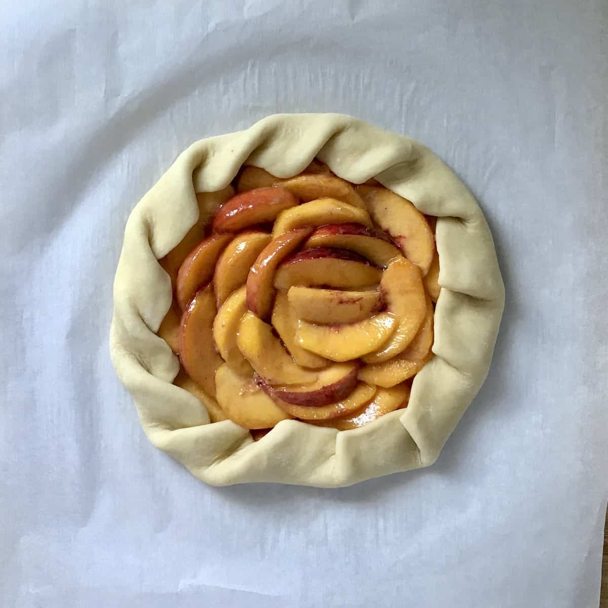 An over head photo of a peach crostata on parchment paper.