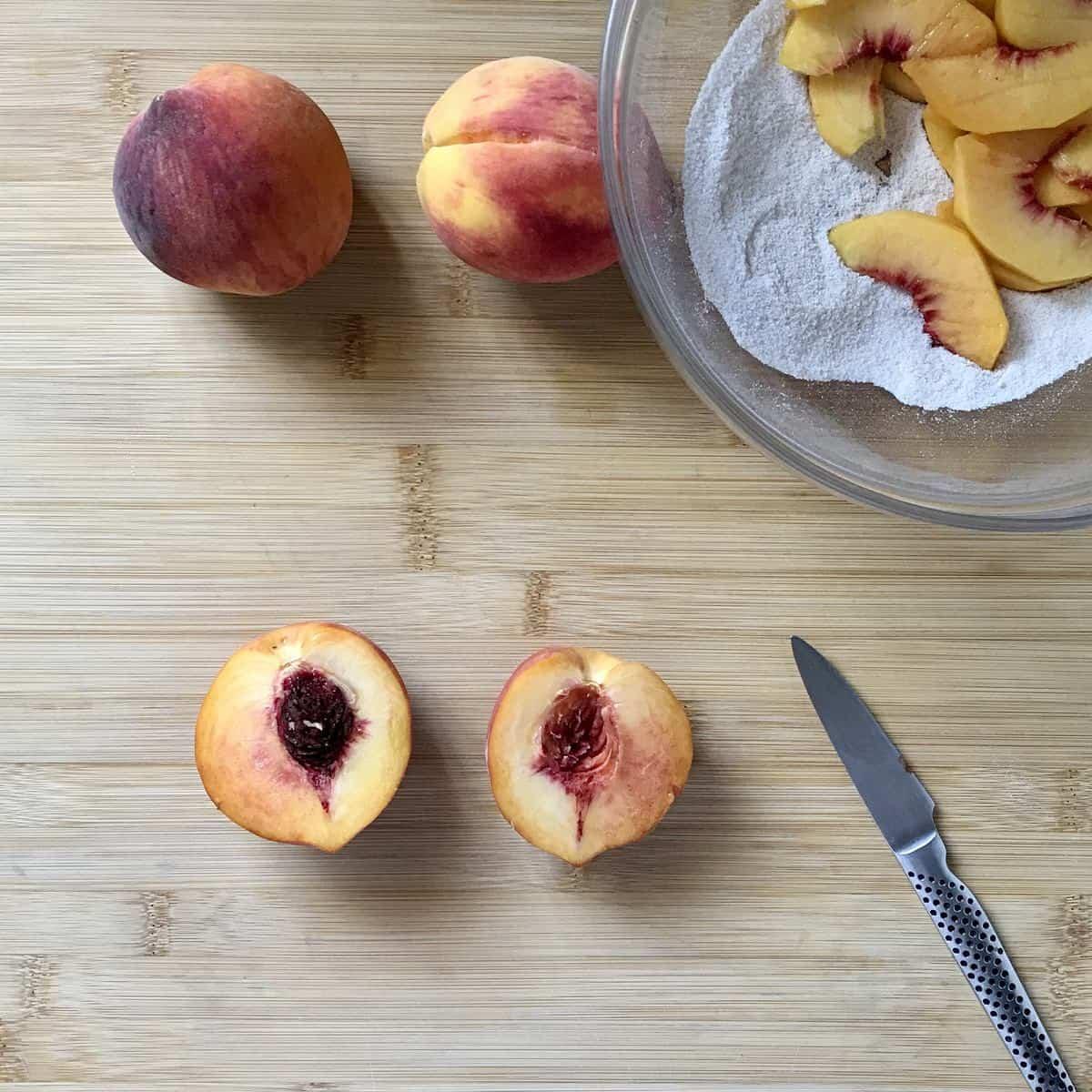 Peach halves on a cutting board.