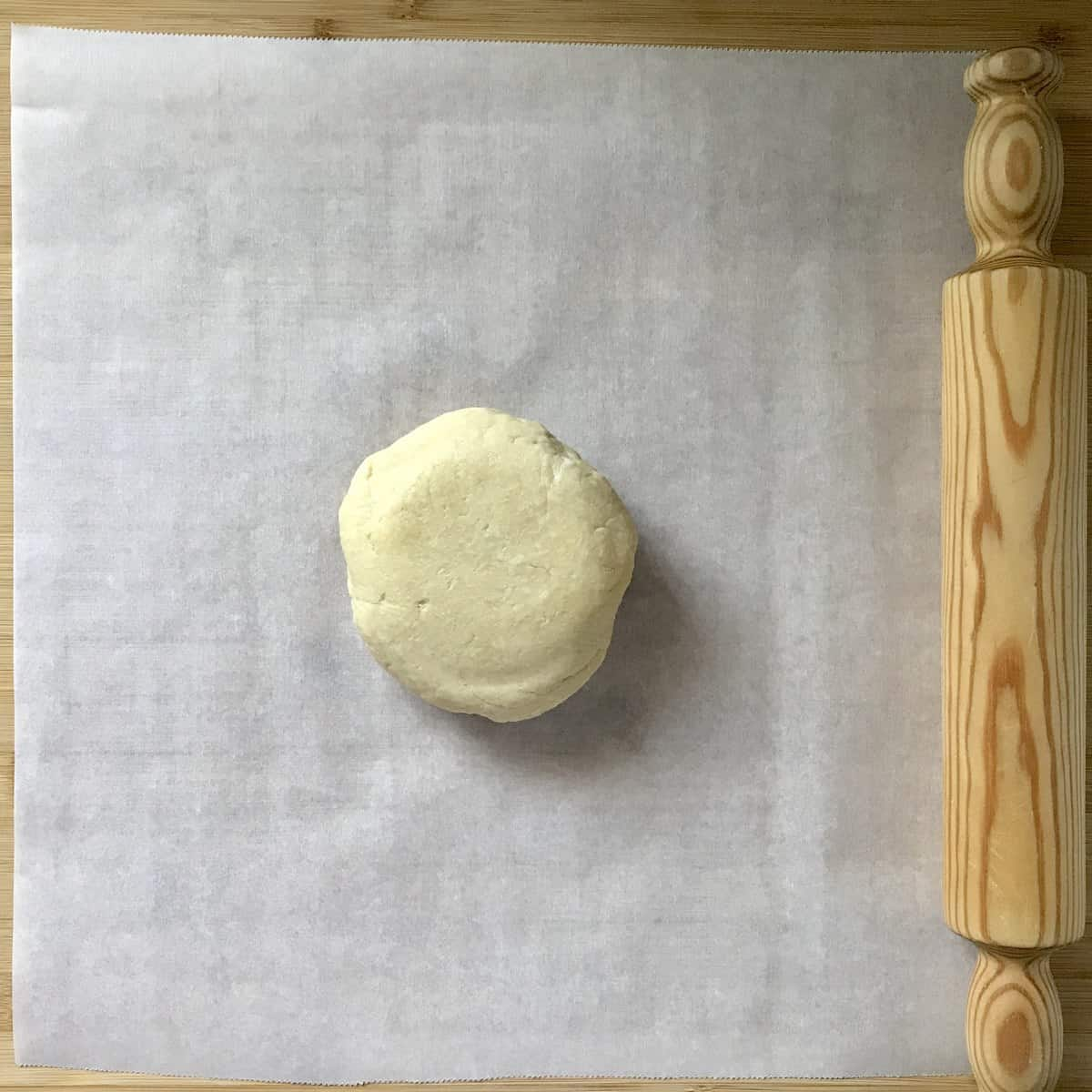 A ball of crostata dough on parchment paper, next to a rolling pin.