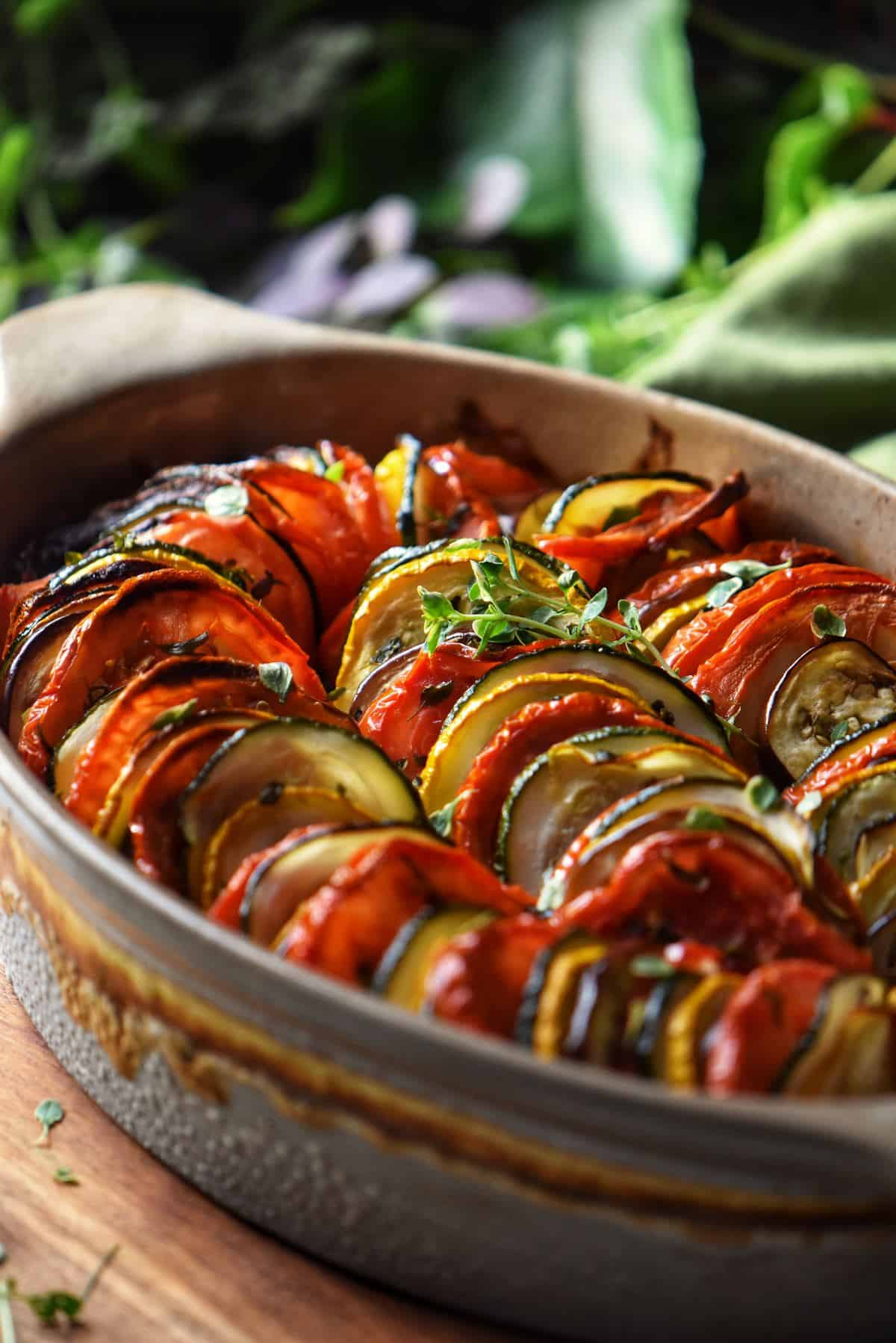 An overhead shot of Mediterranean Roasted Vegetables includes roasted peppers, eggplant, zucchini and tomatoes in a white baking dish.