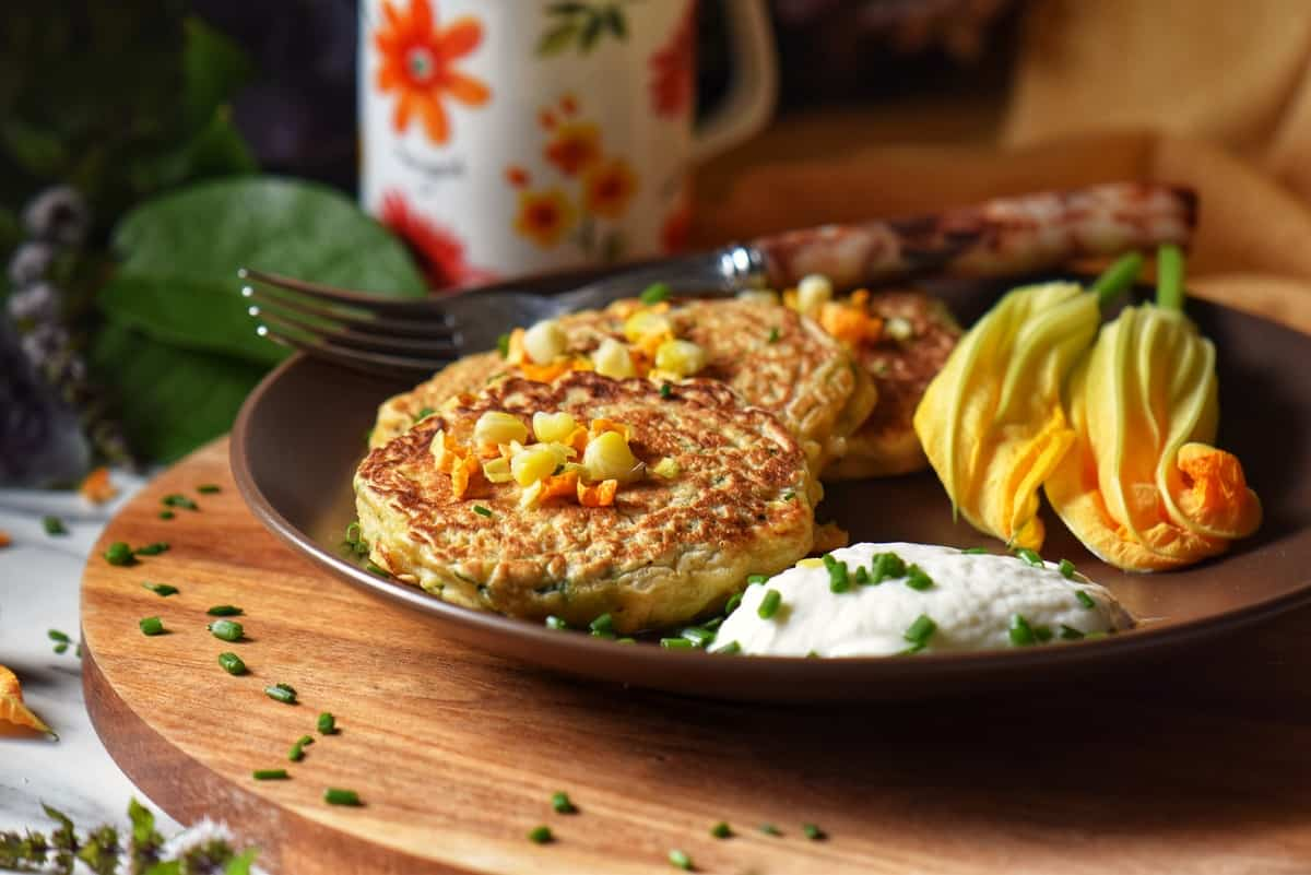 Zucchini pancakes in a plate next to yogurt sauce.