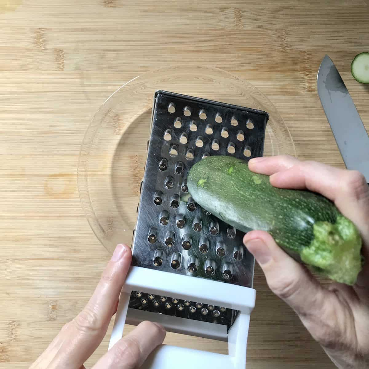 Zucchini being grated with a box grater.