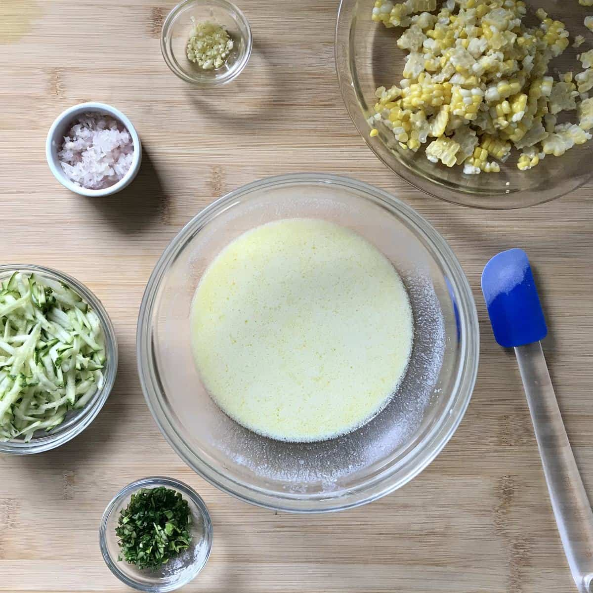 The wet ingredients to make zucchini corn pancakes on a wooden board.