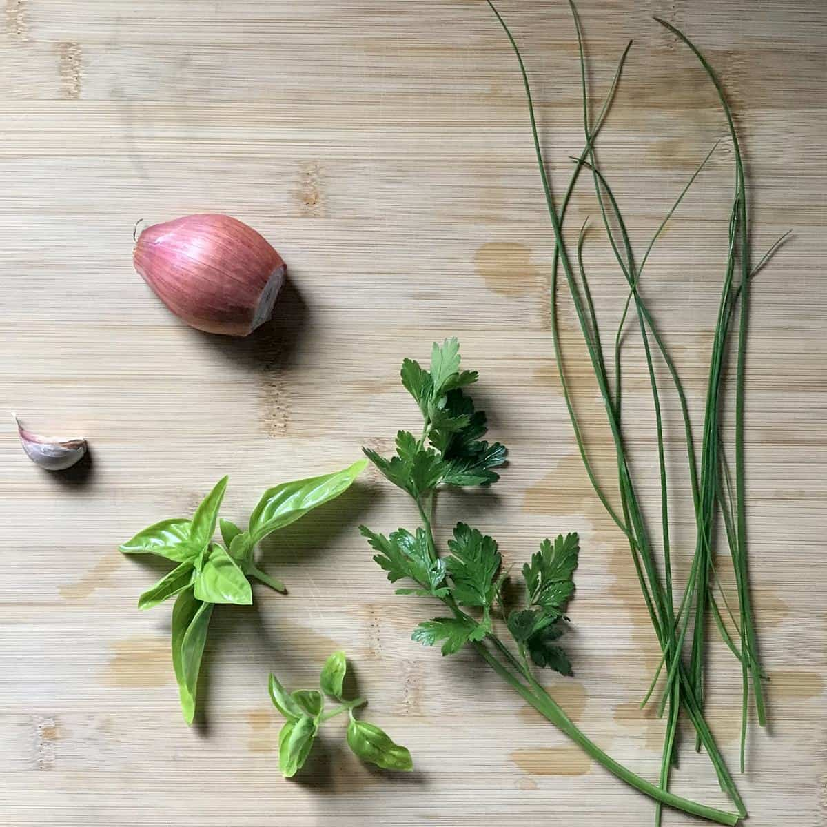 Fresh herbs, garlic and a French shallot on a cutting board.
