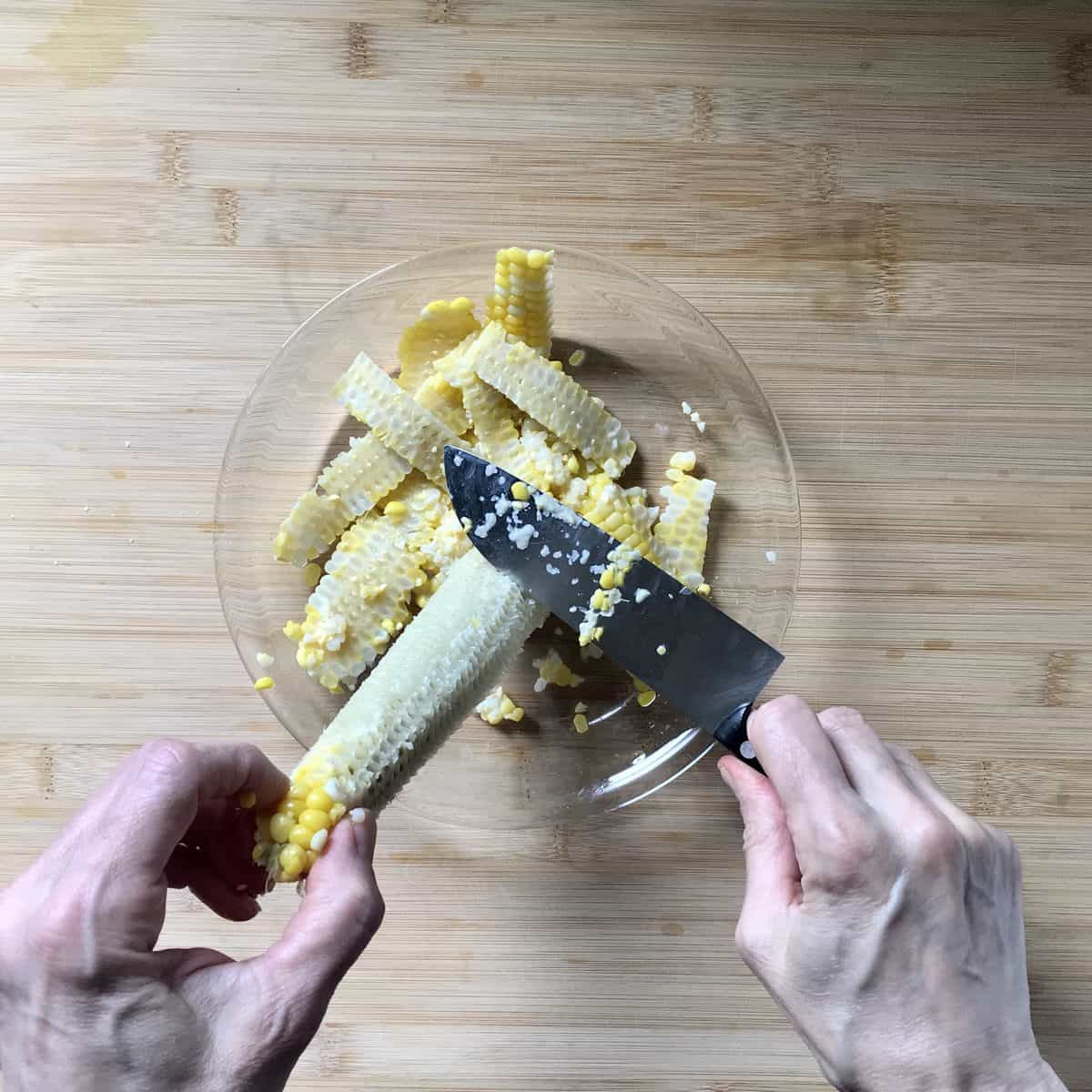 Corn kernels being milked from a corn cob with the back of a knife.
