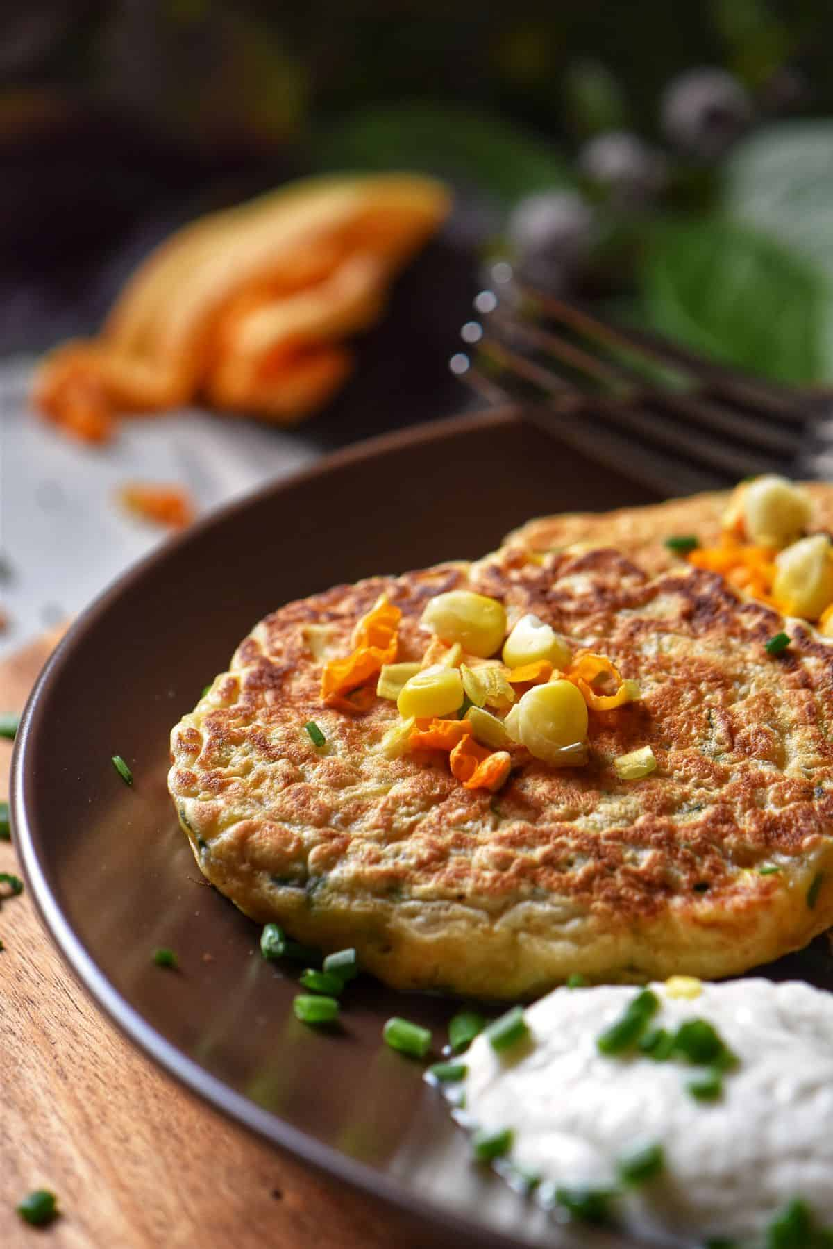 Zucchini pancakes and yogurt sauce in a dinner plate.