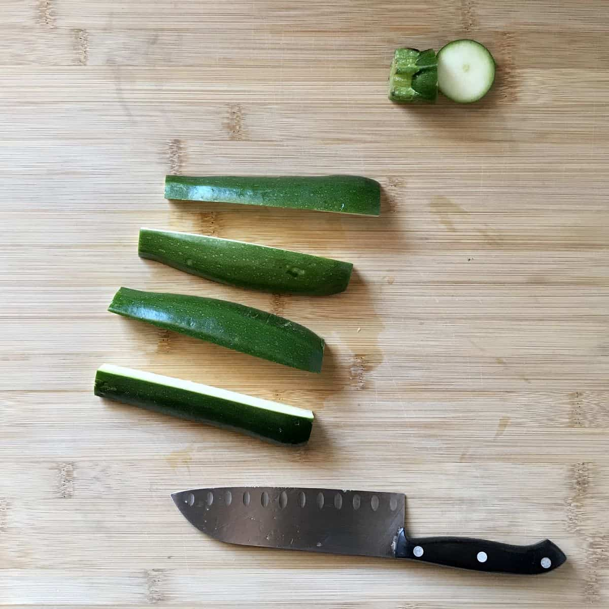 Fresh zucchini next to a knife on a wooden board.