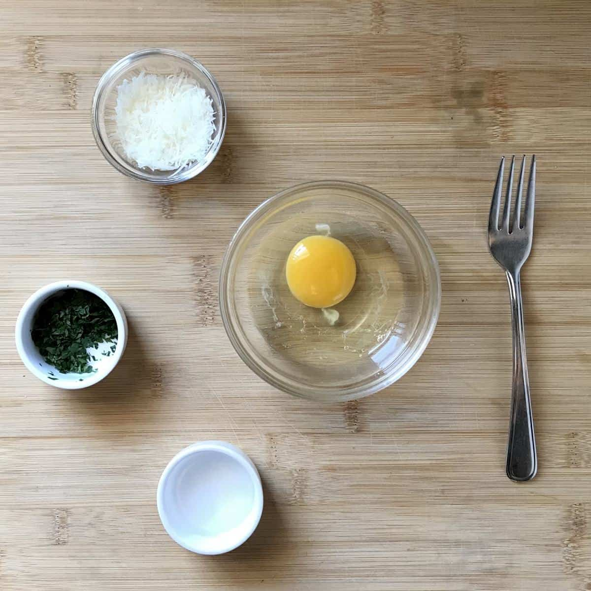 One egg, minced parsley , grated cheese and water in separate bowls on a cutting board.