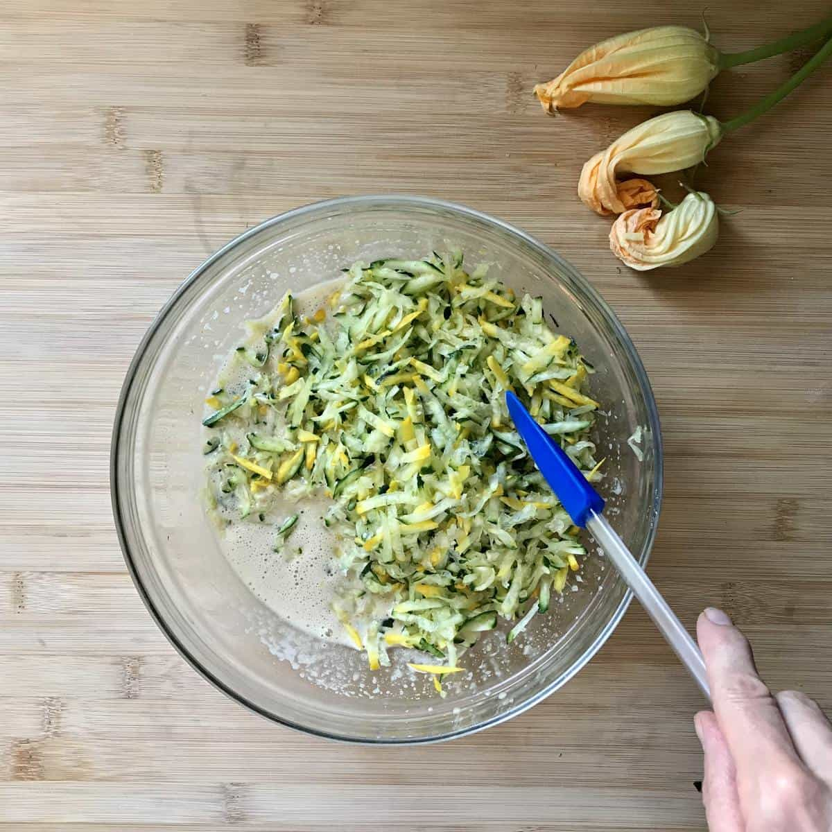Grated squeezed zucchini added to liquid ingredients of zucchini bread in a bowl.