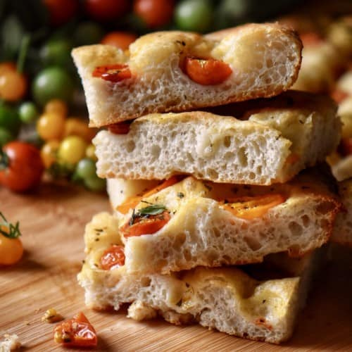 A stack of sliced cherry tomato focaccia bread on a wooden board.