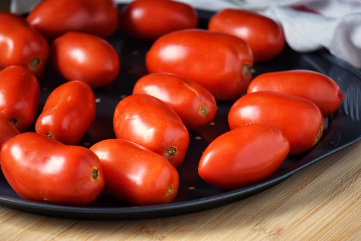 Tomatoes spread out on a pan, ready to be frozen.