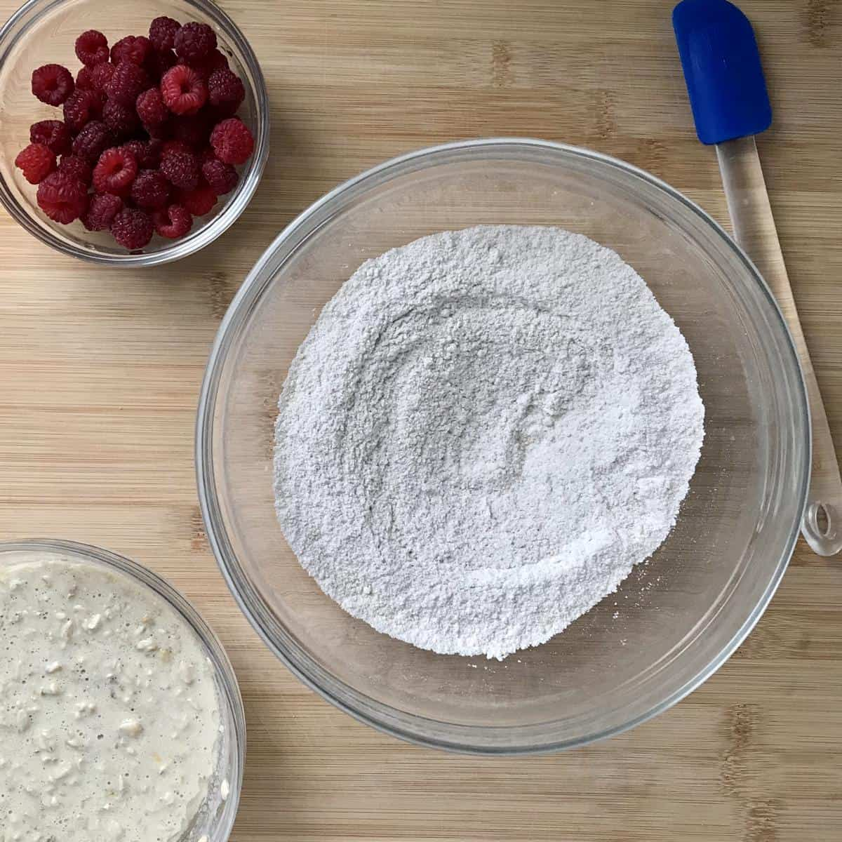 The raspberries along with the wet and dry ingredients in separate bowls.