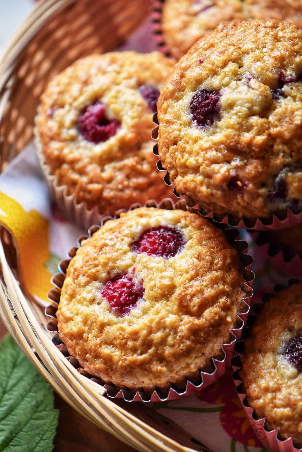 A few raspberry muffins in a wicker basket.