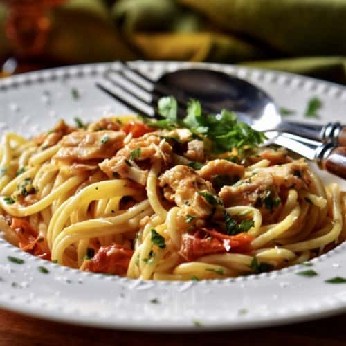 Spaghetti with tuna, garnished with cheese and Italian parsley in a white dish.