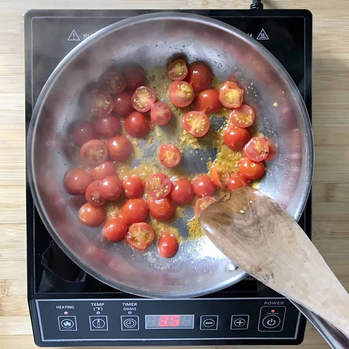 Cherry tomatoes being sauteed in a pan.