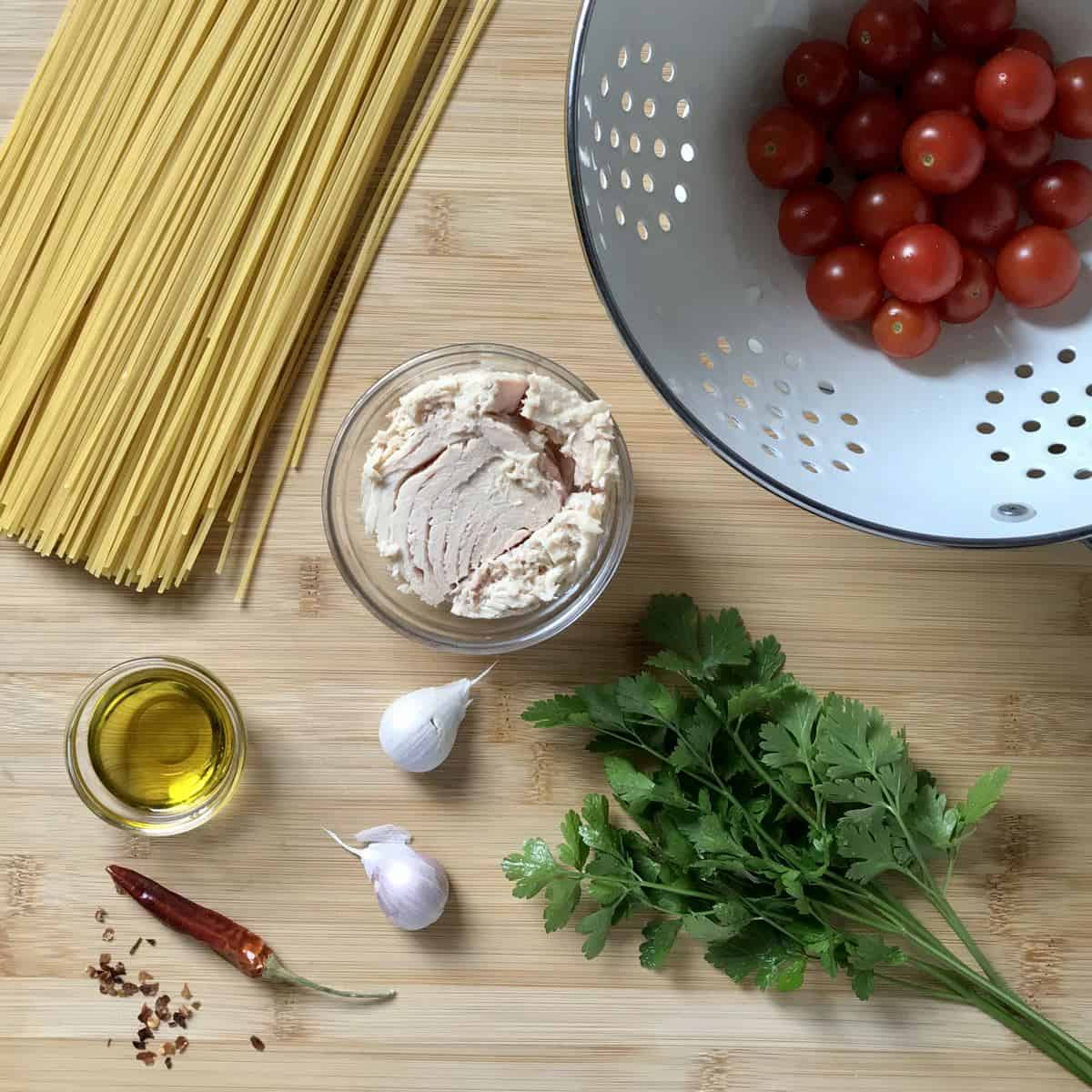 Some of the ingredients to make a tuna pasta recipe on a wooden table.