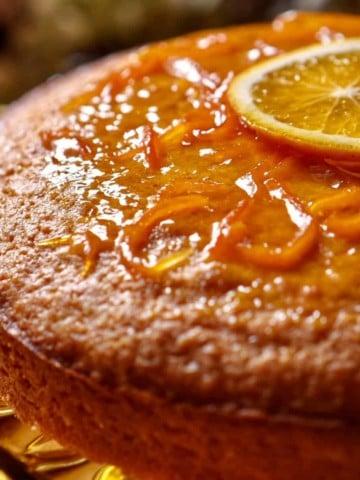 A glazed orange juice cake garnished with one slice of orange.