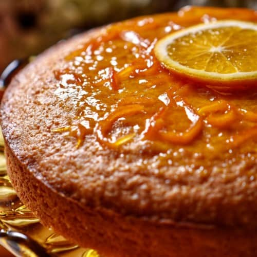 A glazed orange juice cake garnished with one slice of orange.