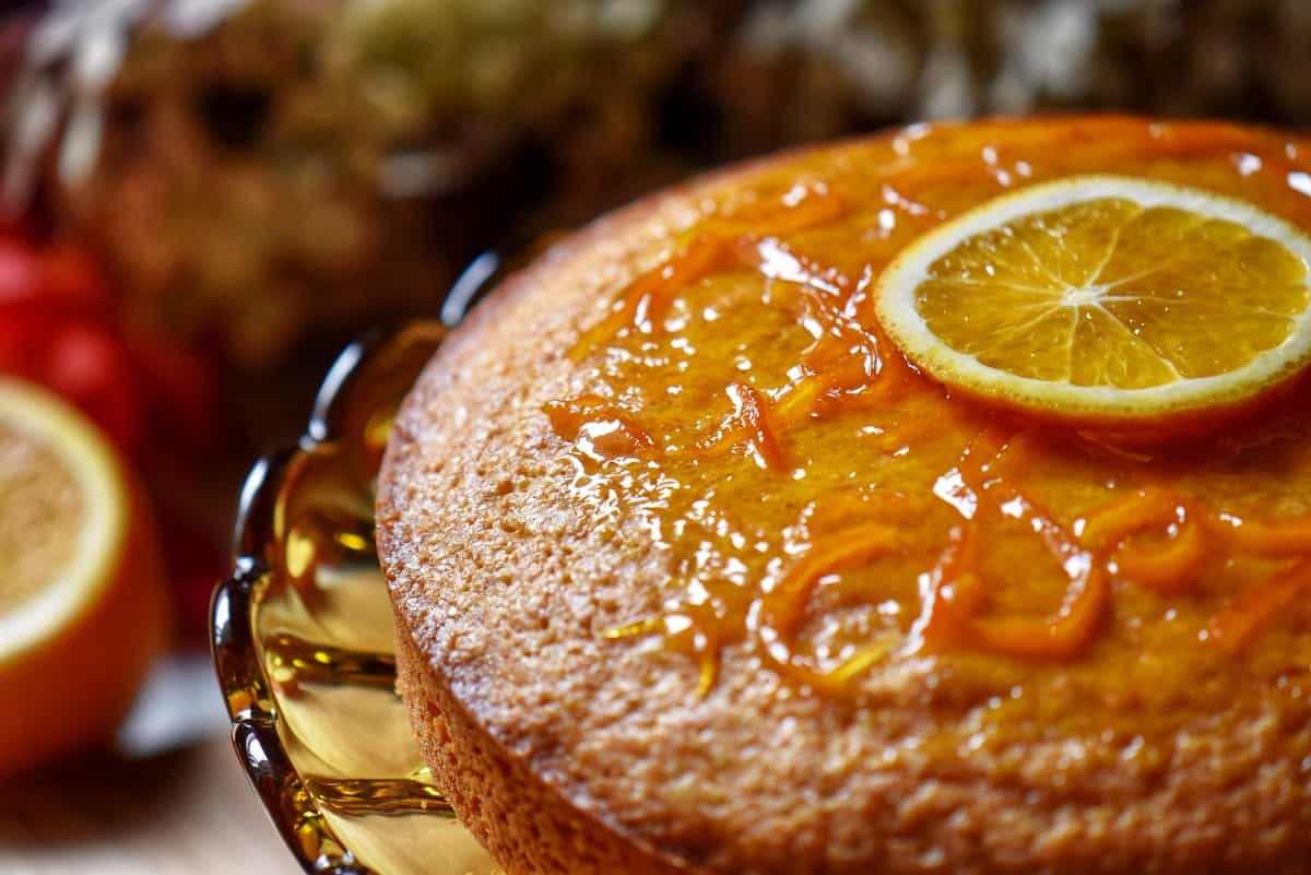 An orange glazed cake on a pedestal.