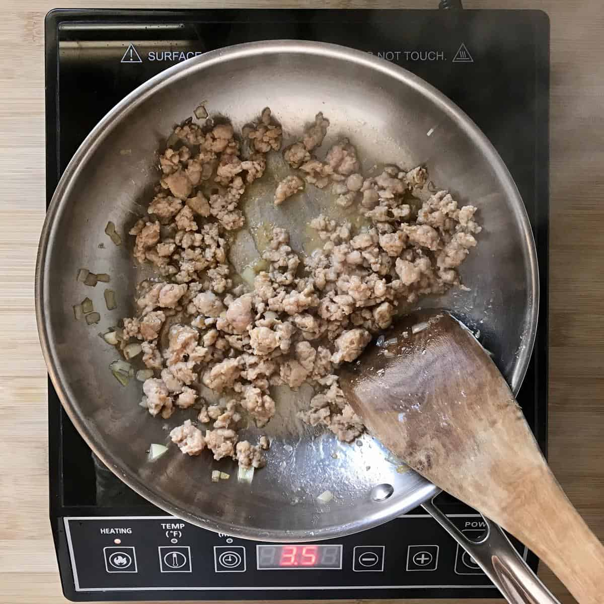 Italian sausage being sauteed in a pan.