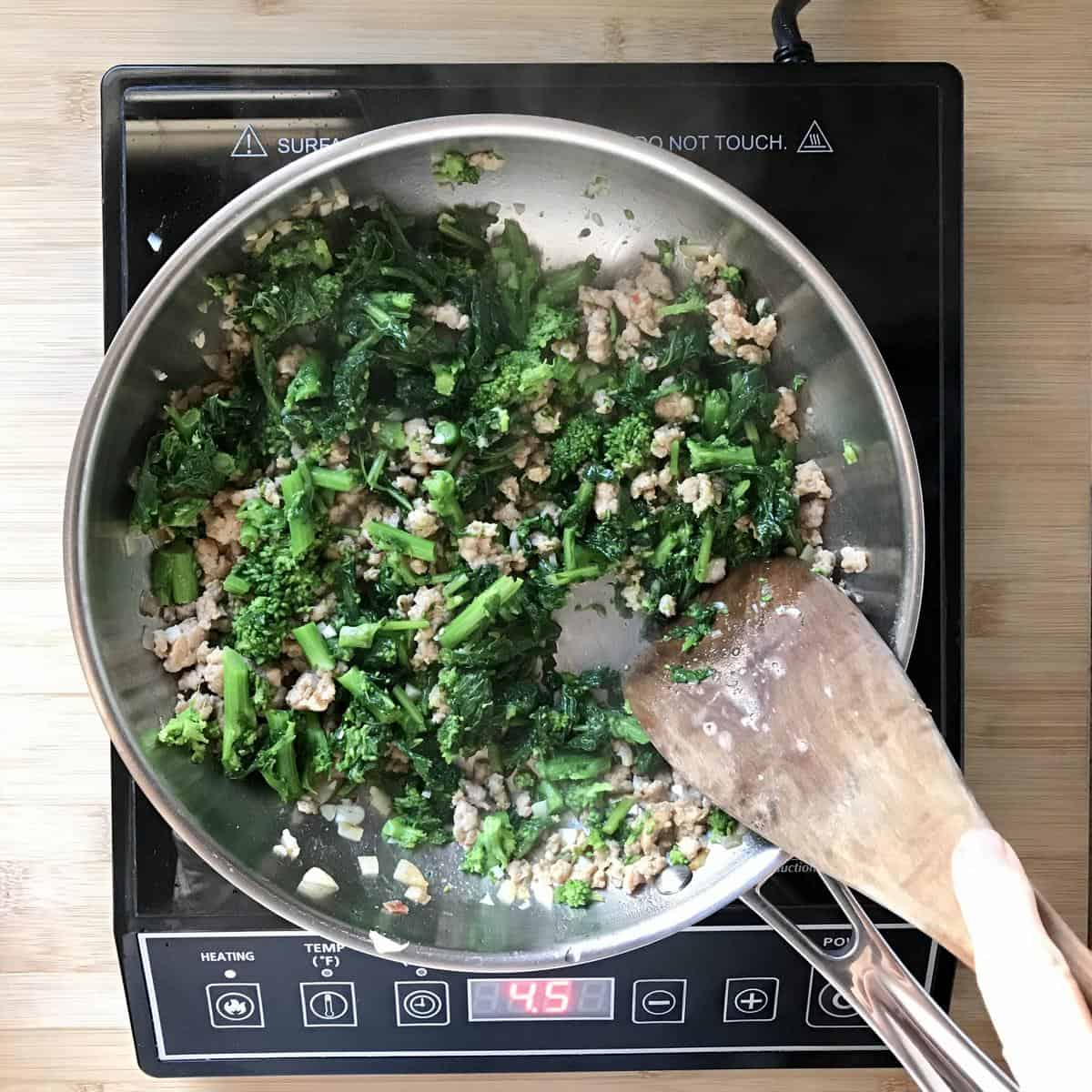 Italian broccoli rabe combined with sausage in a pan.