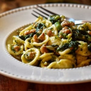 A white plate with orecchiette, Italian sausage and broccoli rabe.