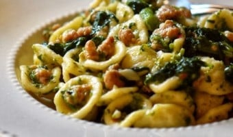 A white plate with orecchiette, Italian sausage and broccoli rabe.