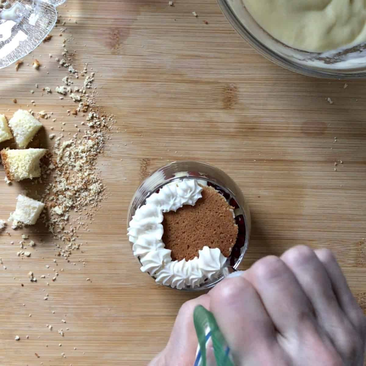 The top layer of the Italian sponge cake is being garnished with whipped ricotta.