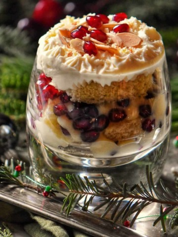 Zuppa Inglese in a glass topped with whipped ricotta on a silver platter.