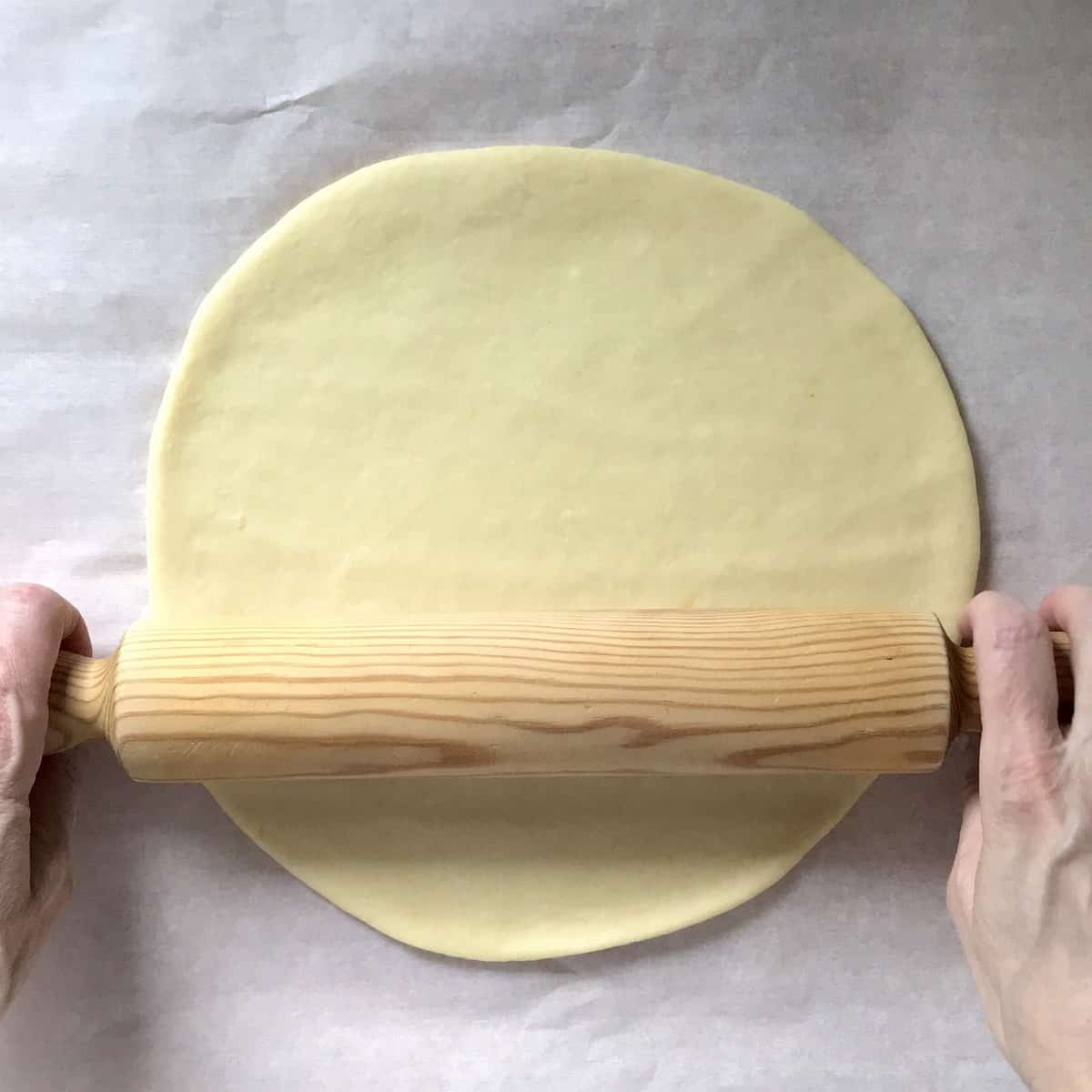 A ball of dough being rolled into a circle with a rolling pin.