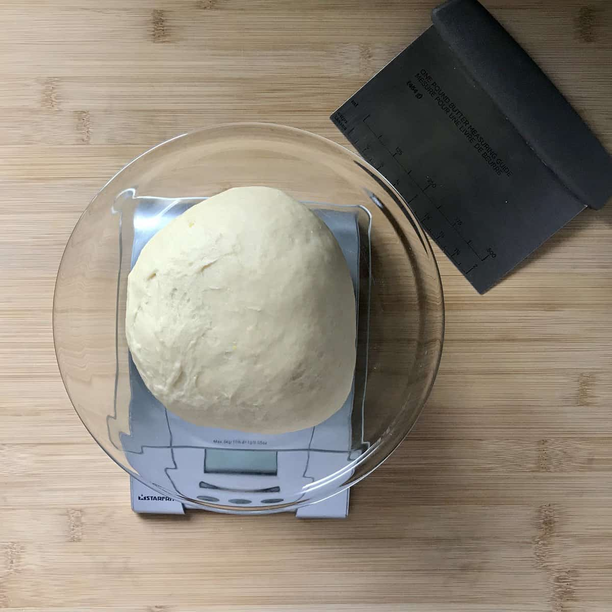 A ball of yeast dough being weighed on a scale.