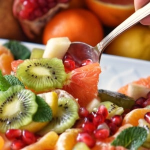 Fruit salad being picked up with a spoon.
