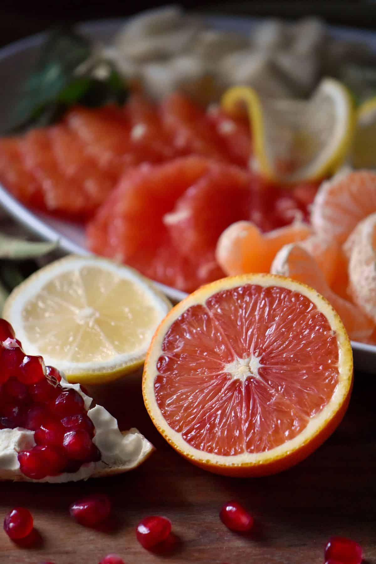 Cara Cara oranges, lemons and a pomegranate being prepared to make a winter fruit salad.