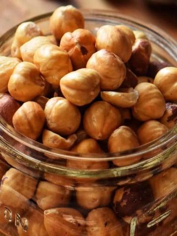 A close up of roasted hazelnuts in a mason jar.