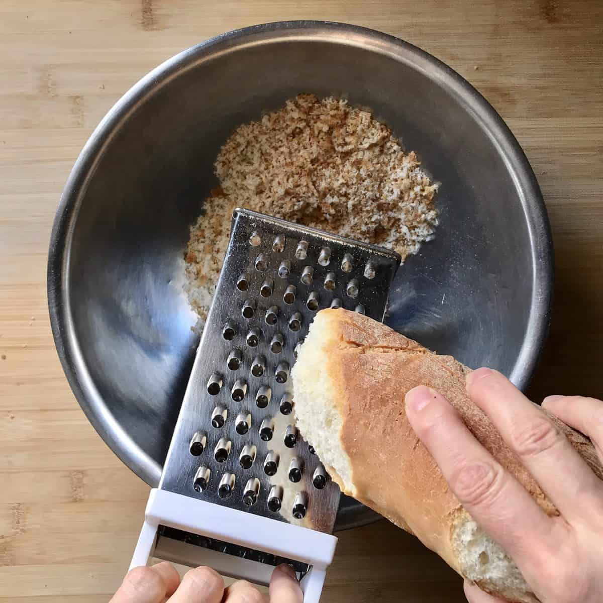Day old bread in teh process of being grated.