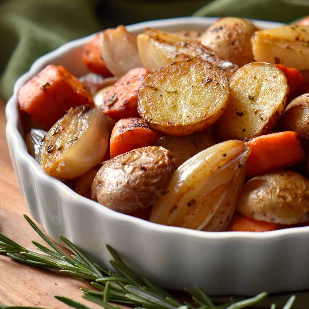 Oven roasted small potatoes and carrots in a white dish.