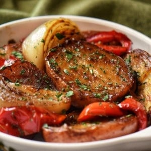 Roasted Red Potatoes, caramelized onions and roasted bell red peppers in a white dish.