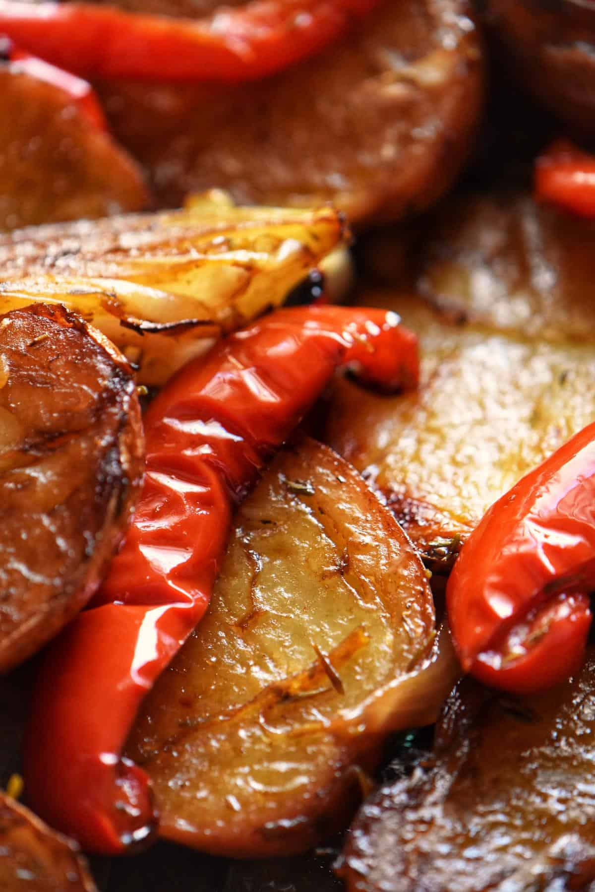 Roasted potatoes and red bell peppers in a baking dish.