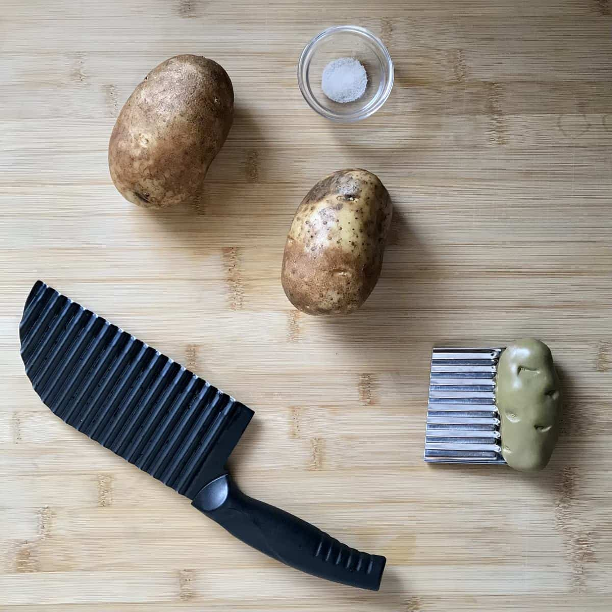 Crinkle cut knives and russet potatoes on a wooden board.