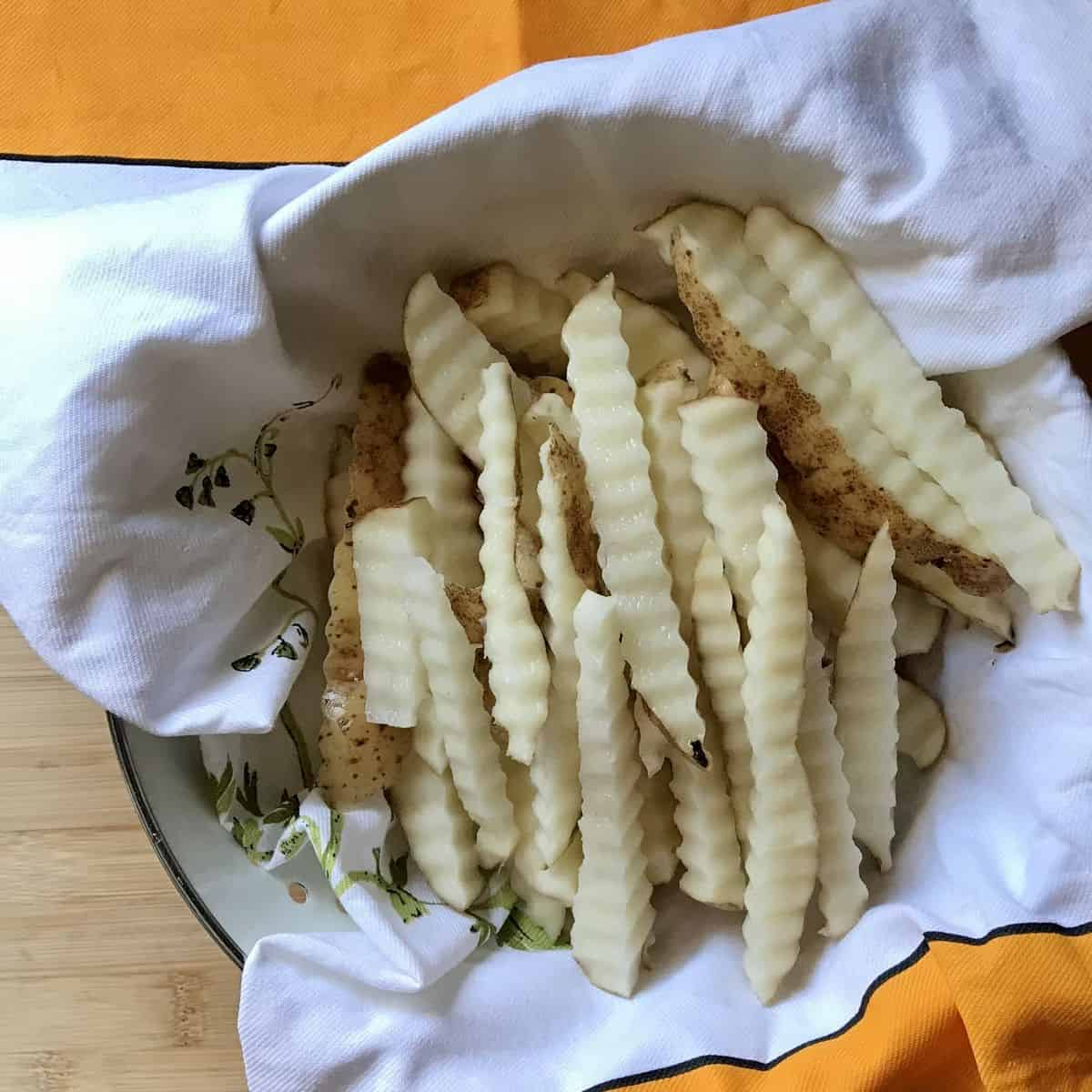 Wavy fries in the process of being dried with a tea towel.