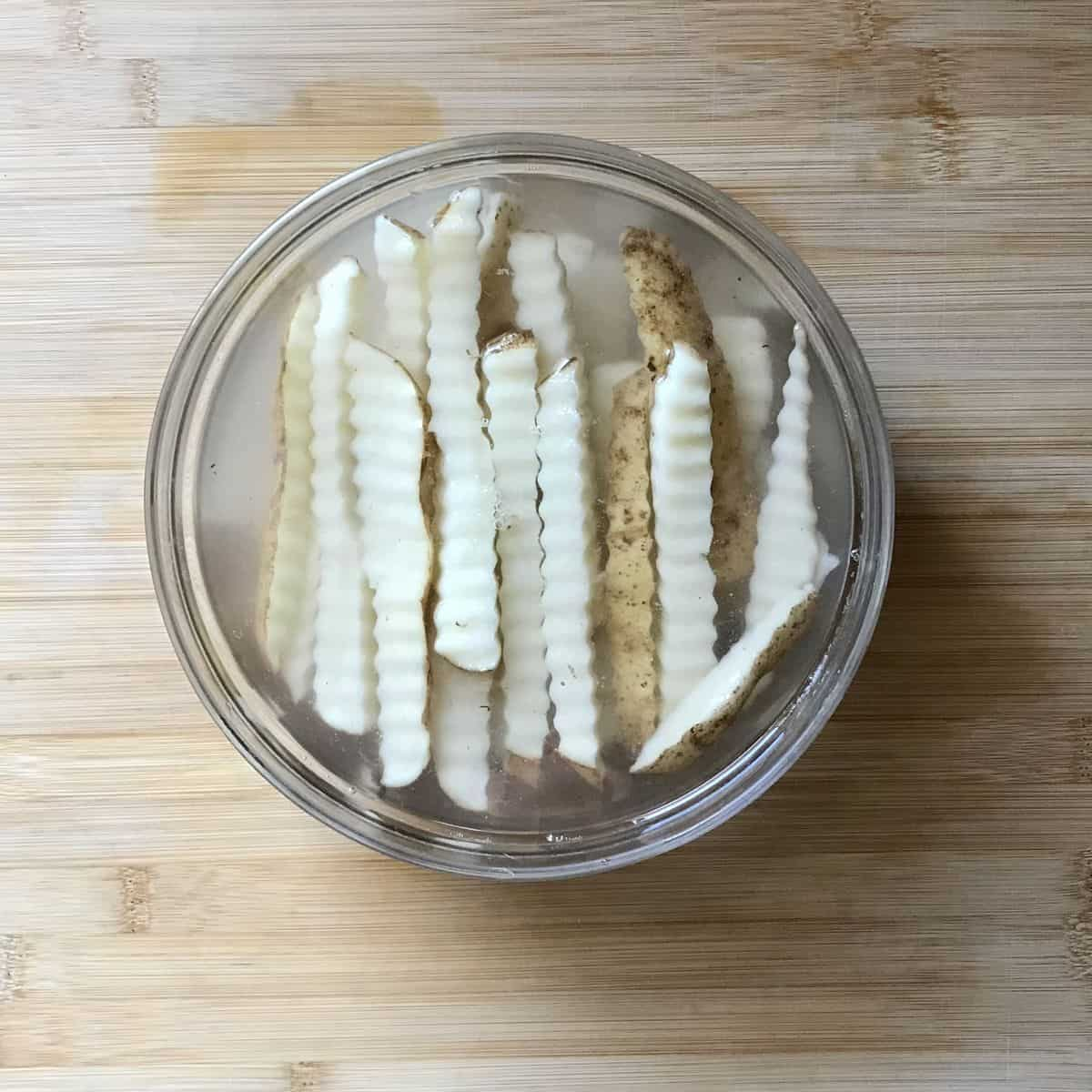 Crinkle cut potatoes soaking in a bowl of water.