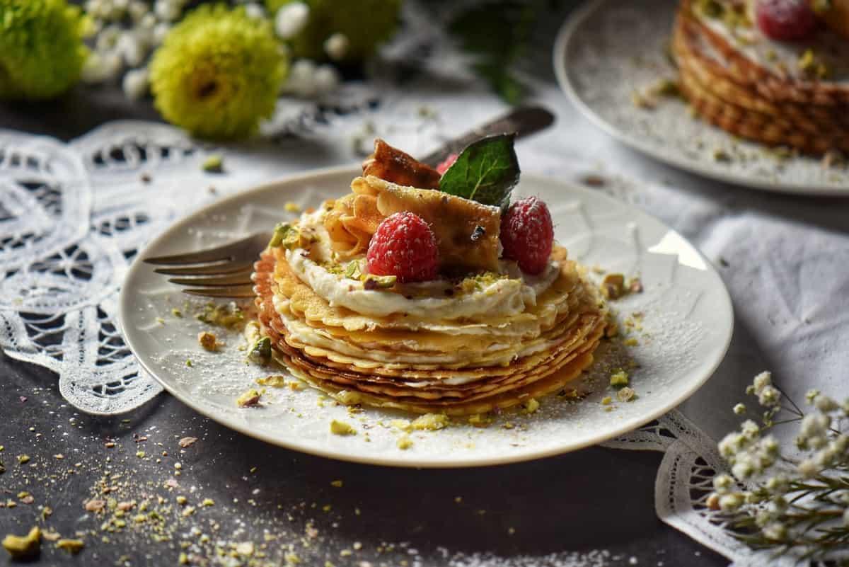 A mini crepe cake garnished with ricotta, raspberries and icing sugar.