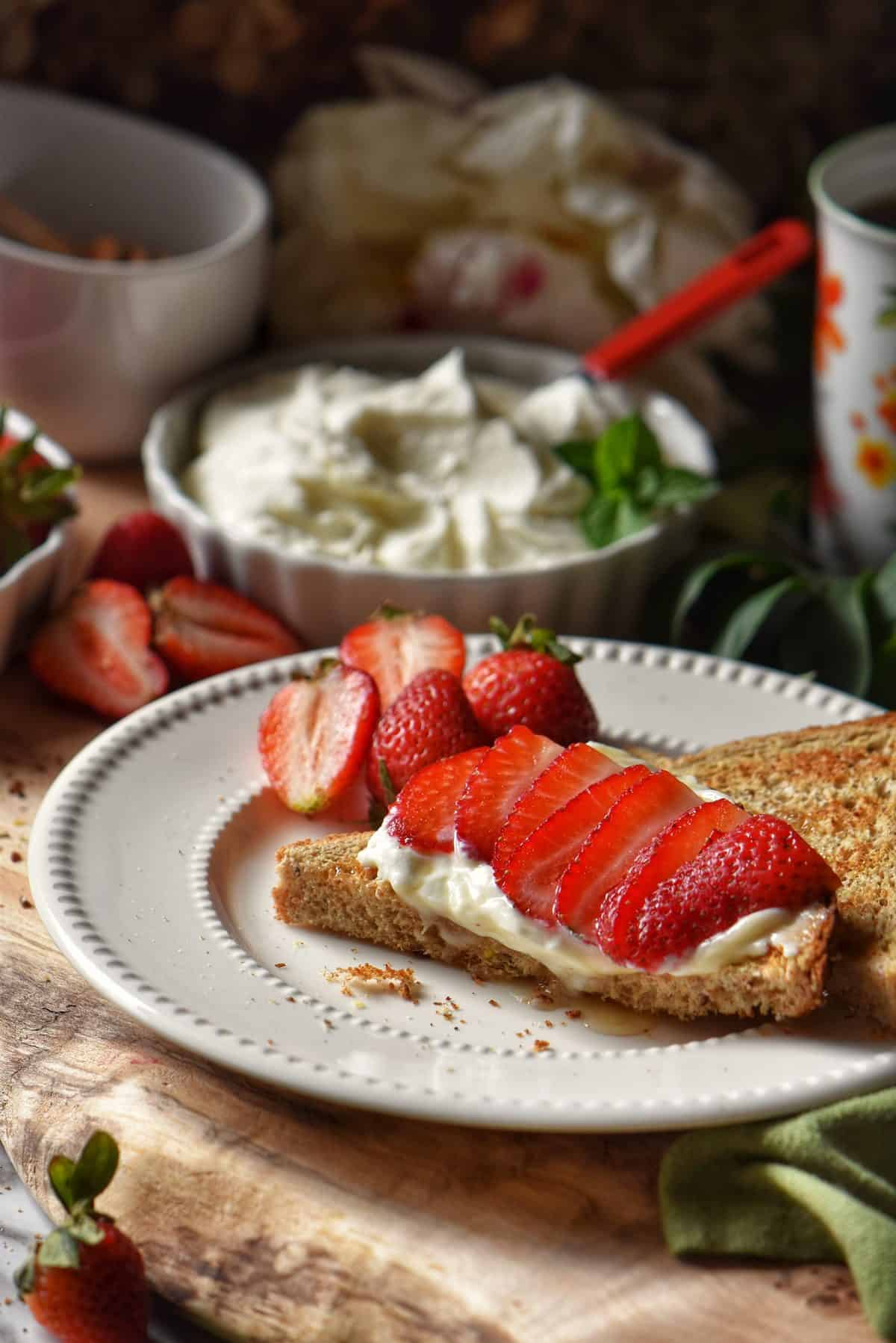 Toast on a white plate garnished with ricotta and strawberries.