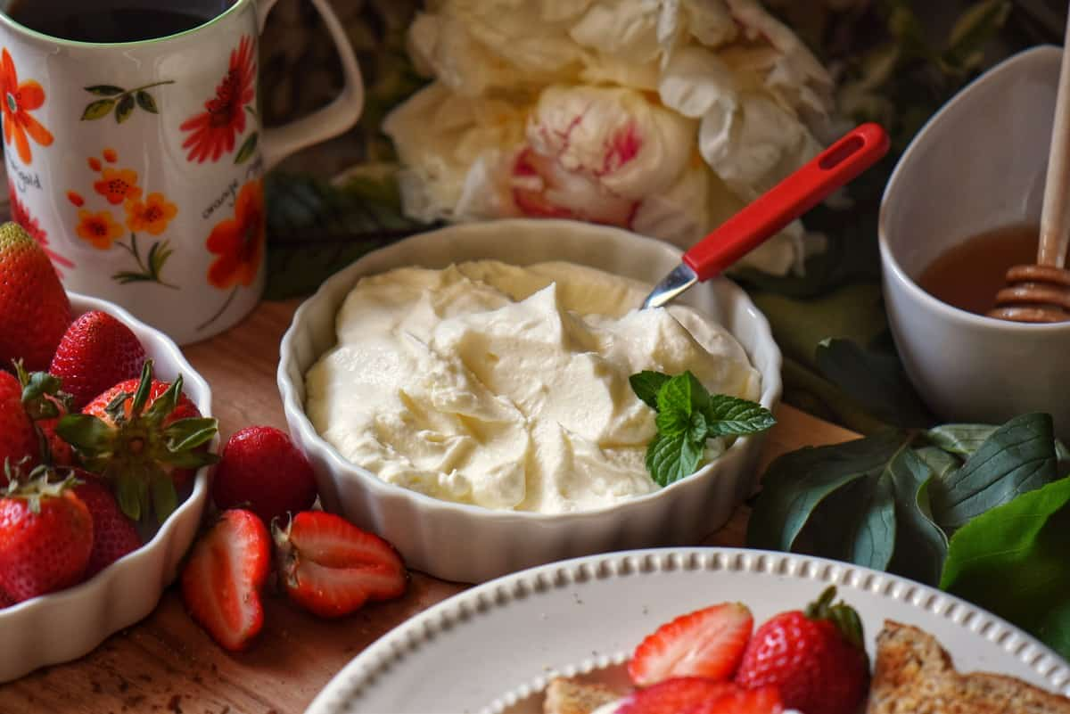 A bowl of ricotta surrounded by strawberries.